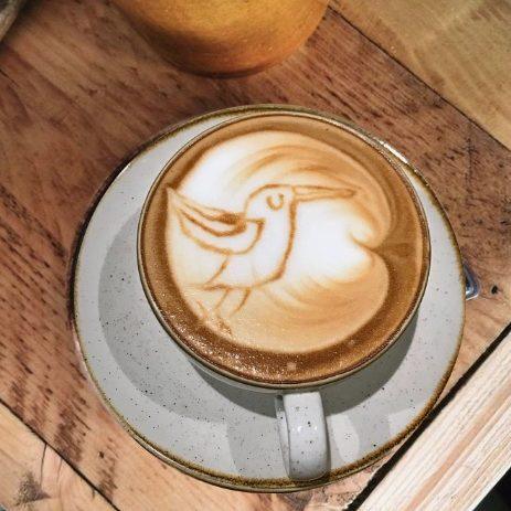 Il cappuccino vegetale con il latte d'avena heaven barista e il suo logo dell'uccellino blu rappresentati tramite latte art.